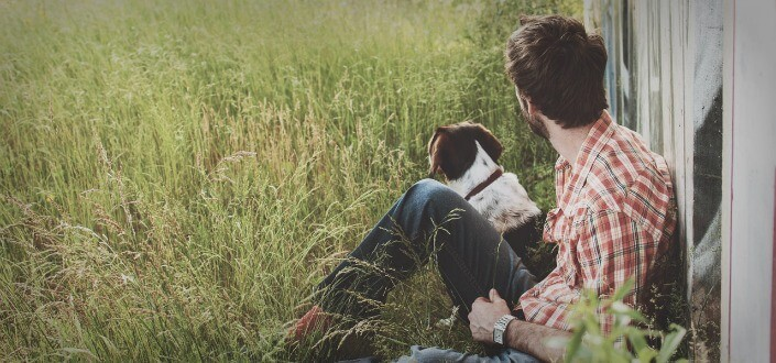 Guy sitting on grass with his dog