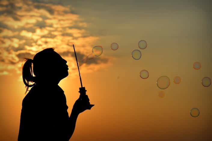 Girl blowing into bubbles at sunset