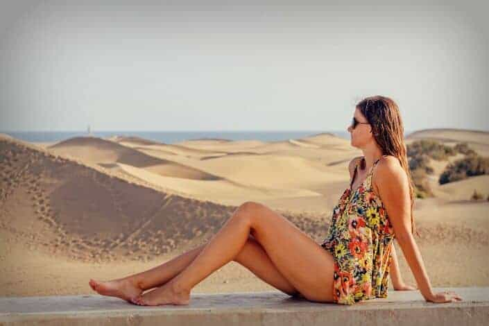 Girl sitting on a ledge before sand dunes