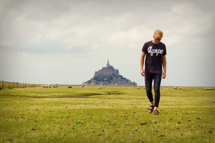 Guy walking on a grassy field with a tall structure behind him