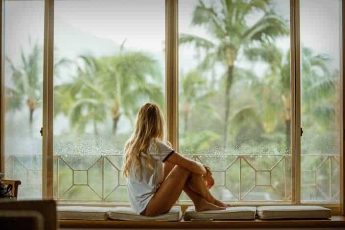 Girl sitting by a large window staring into coconut trees