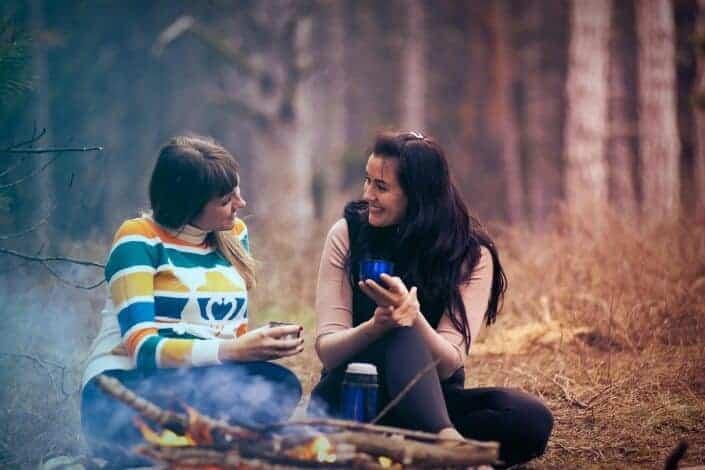 Two girls enjoying a hot beverage while camping