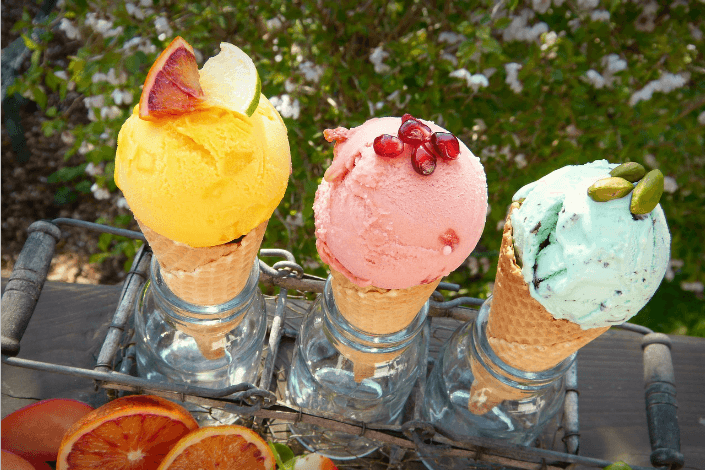 Three cones of different flavored ice cream with toppings