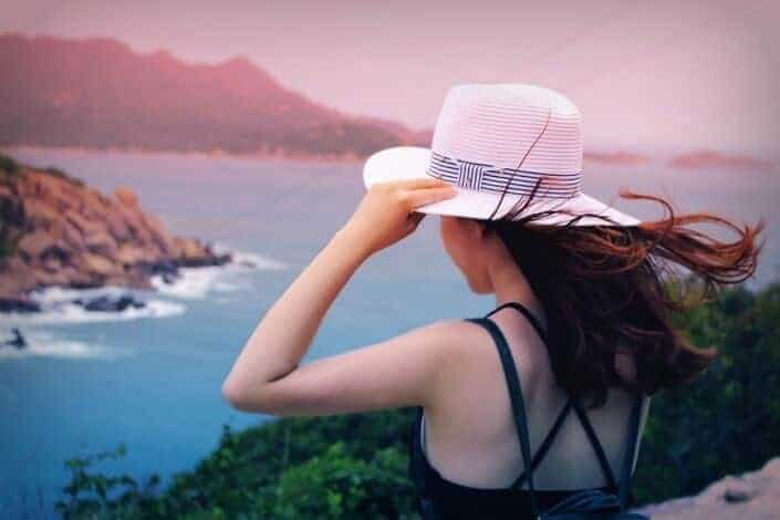 Girl holding her hat while looking out from a cliff