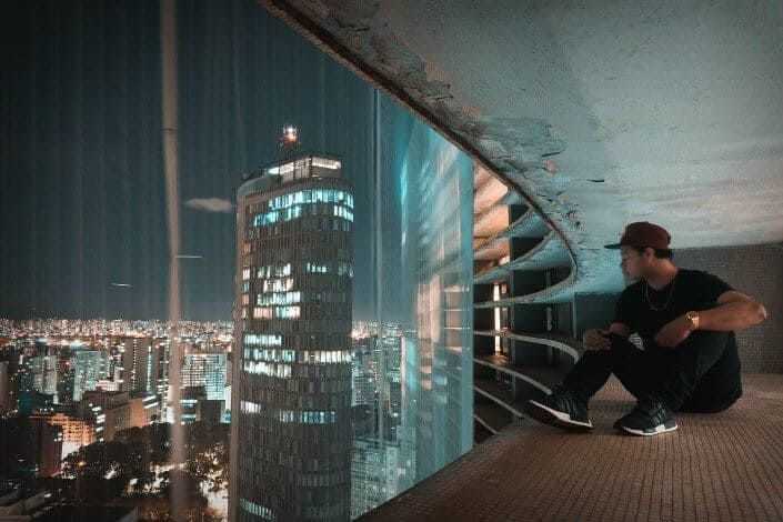 Guy sitting on building ledge with glass covering