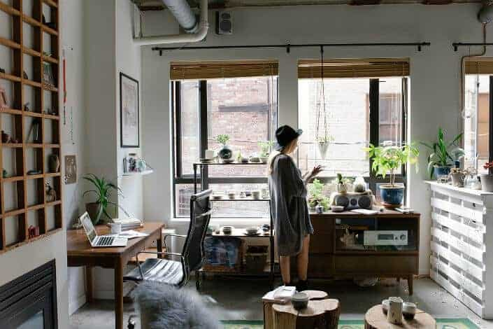 Hipster girl standing in her apartment.