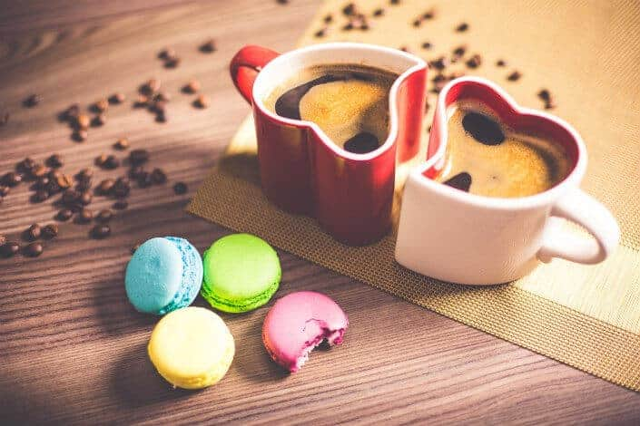 Heart shaped mugs with coffee beans and four macarons.