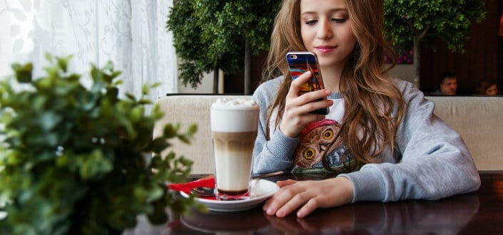 Girl capturing her coffee with her phone.