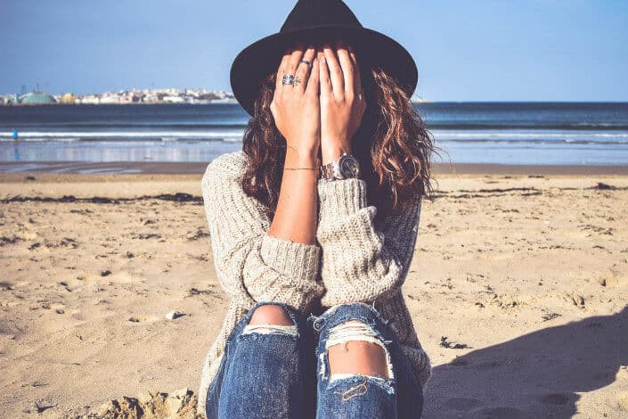 Girl in a beach covering her face with her hands.