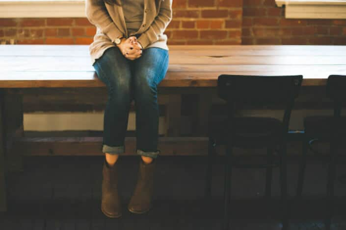 Girl sitting on a long wooden table.