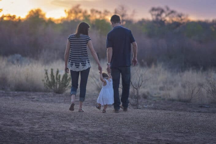 Couple holding hands with their little girl walking on a field.