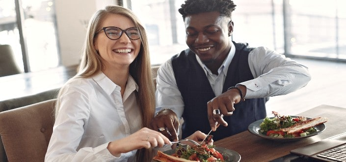 Couple laughing while guy slices into girl's salad