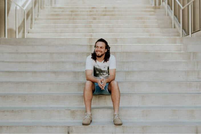 man sitting on stairs smiling