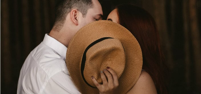 couple covering their kiss with a hat