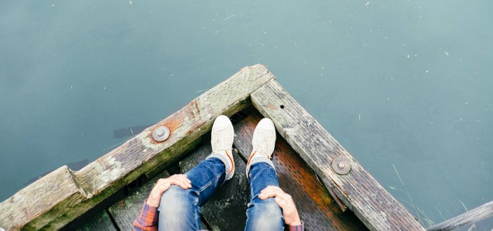 Man sitting on edge of wooden platform