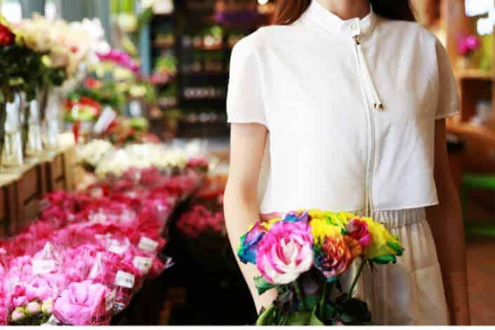 Woman holing a flower inside a flower shop