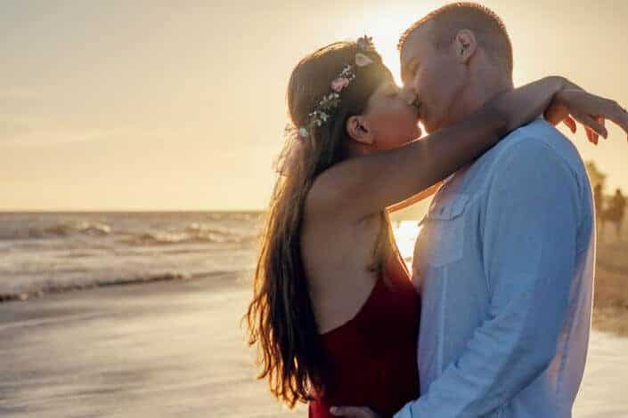 Couple kissing on the beach by sunset