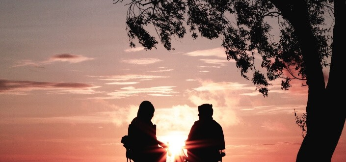 silhouette of two person sitting near tree