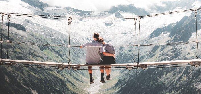 couple sitting on hanging bridge at daytime
