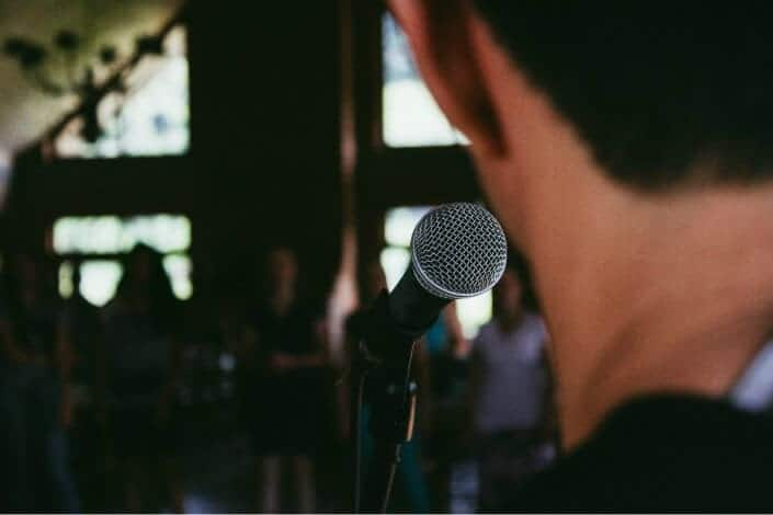 Man speaking thru the microphone in front of an audience.