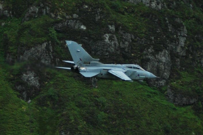 A jet flying over the lavish mountains.