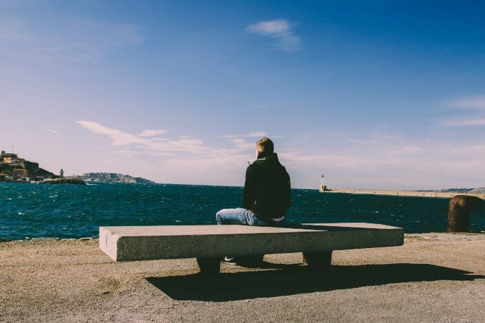 man sitting in bench and watching the sea