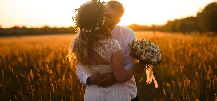 Newlywed kissing in the field