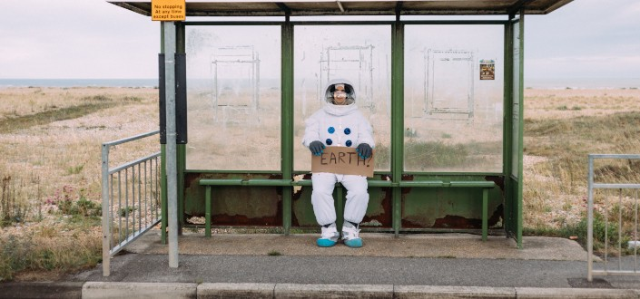 Astronaut-attired person holding a sign _Earth_ at a waiting shed.