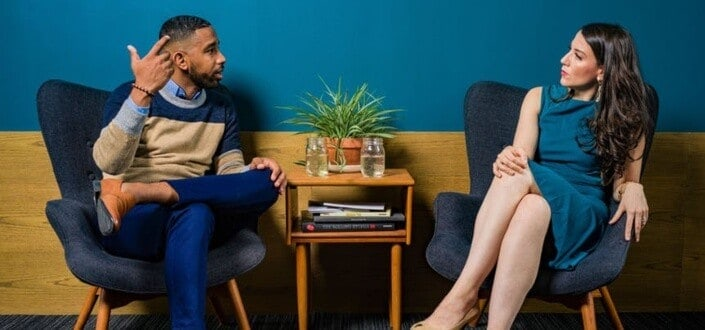 Man explaining something while woman listens attentively