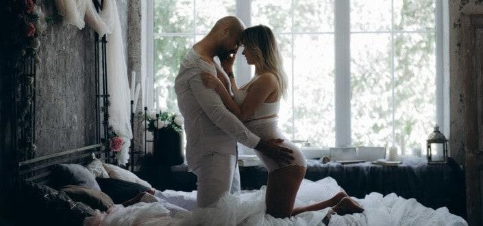 couple kneeling on bed head to head