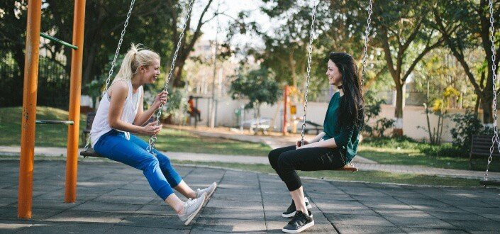 Two girl friends chatting on a swing.
