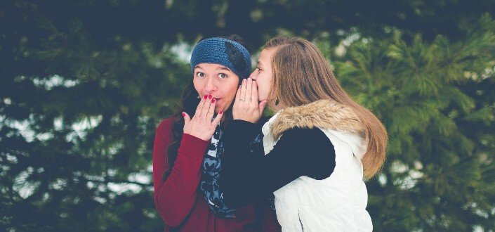 A girl whispering something to her bestfriend.