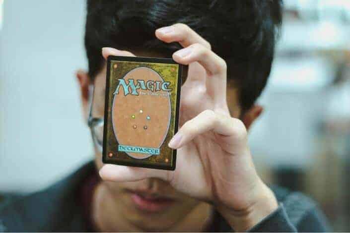 Guy holding a magic card.
