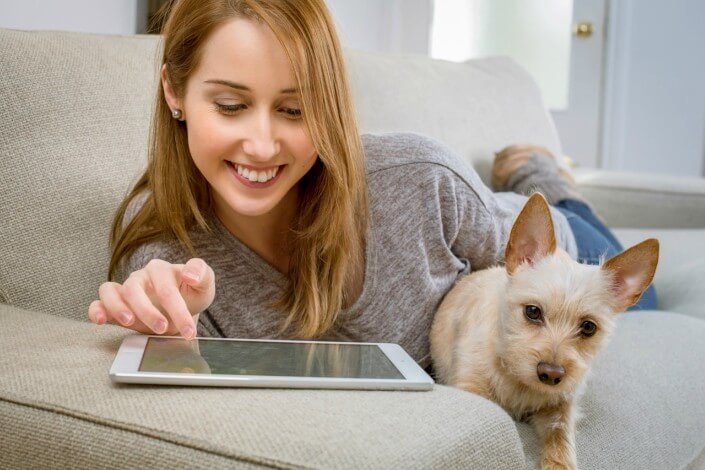 Girl looking at her tablet on a couch smiling with her dog beside her.