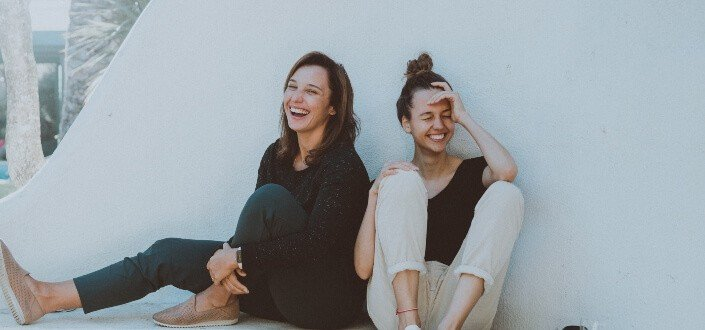 Two girls laughing while sitting beside each other.