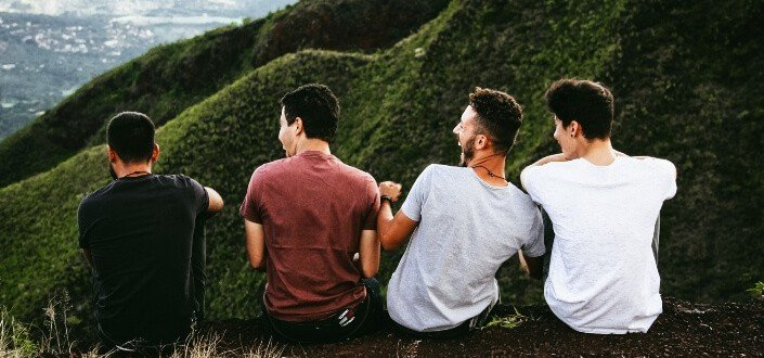 Four guys sitting on a hill.