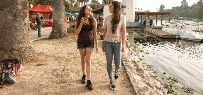 Two girls walking beside seawall.