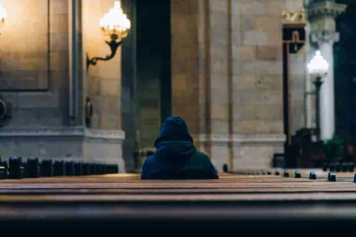 Guy sitting in a church pew.