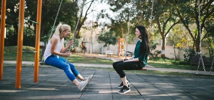 Two women sitting in park swings