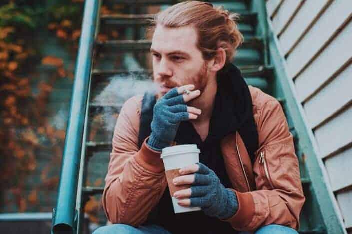 Man smoking while drinking coffee