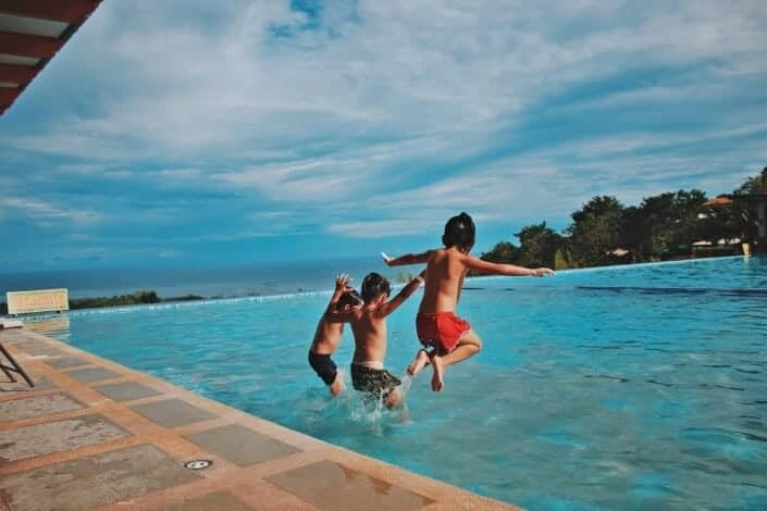 three kids jumping on the pool
