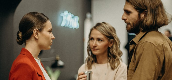 two people listening to a woman talk