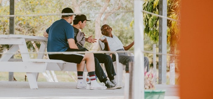 three men talking to each other