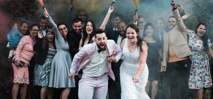 Newlywed couple candidly posing with their guests behind them