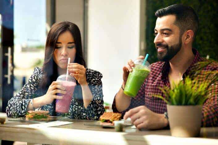 Man and woman drinking smoothie