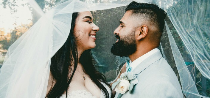 newlywed couple smiling at each other