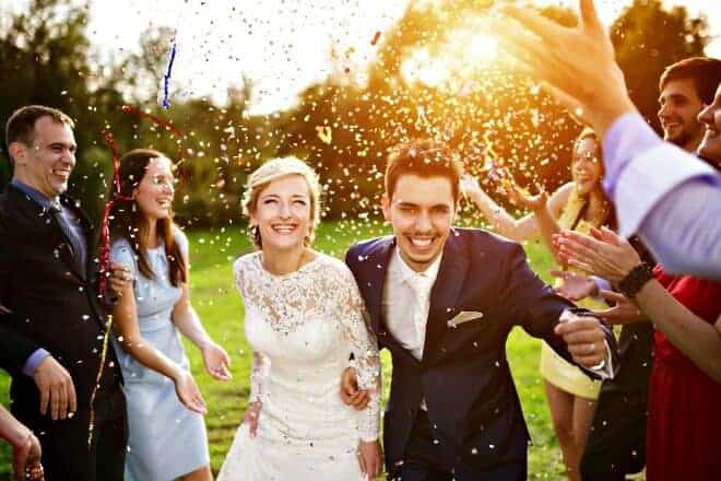 wedding guests throwing confetti at a couple