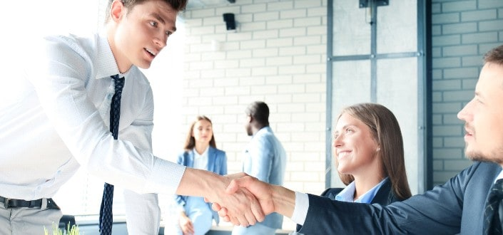 Male applicant shaking hands with the interviewers.