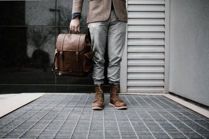 Man in formal attire holding his bag