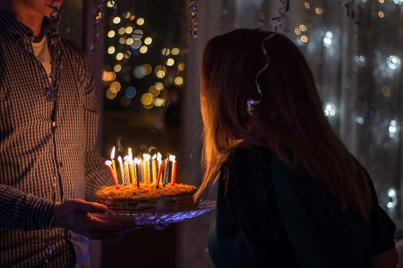 A woman looking at cake with lit candles